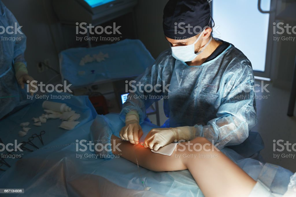 doctor and an assistant in operating room for surgical  clinic stock photo