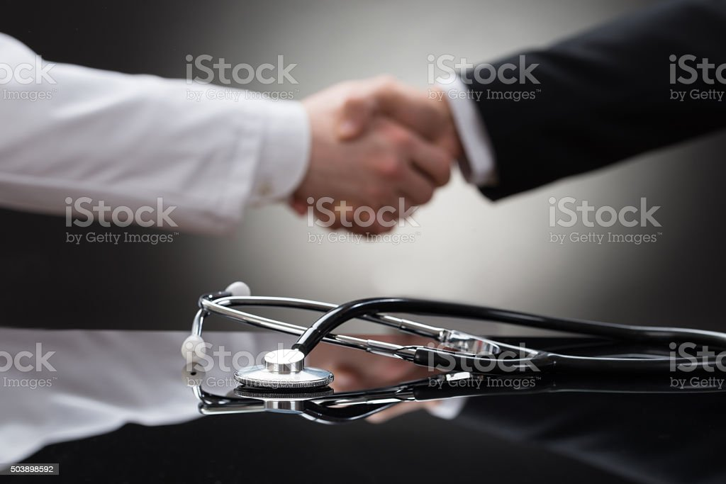 Doctor And Businessman Shaking Hand stock photo