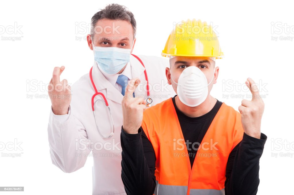 Doctor and constructor showing fingers crossed gesture stock photo