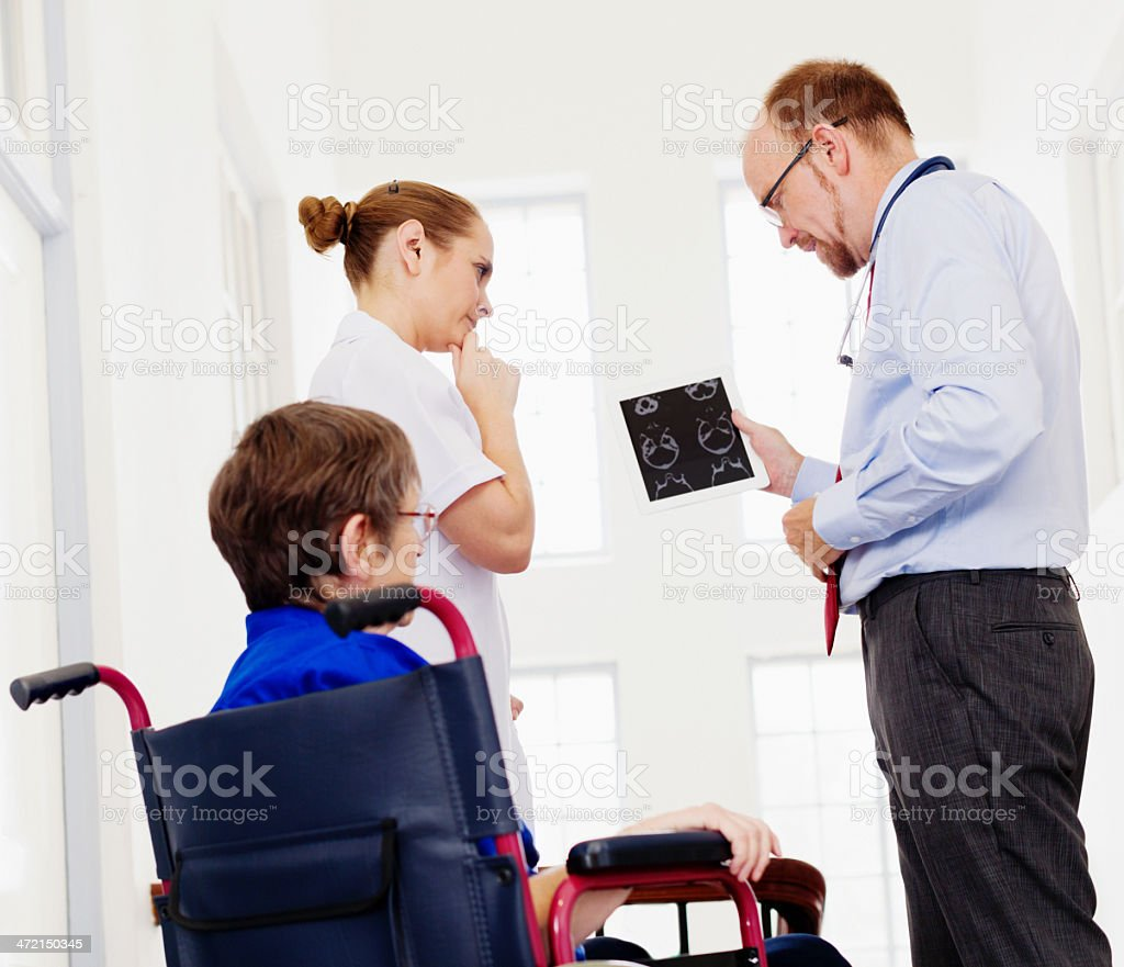 Doctor and nurse confer seriously over elderly woman's CT scan stock photo