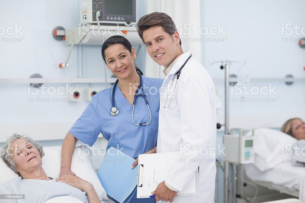 Doctor and nurse next to a patient royalty-free stock photo