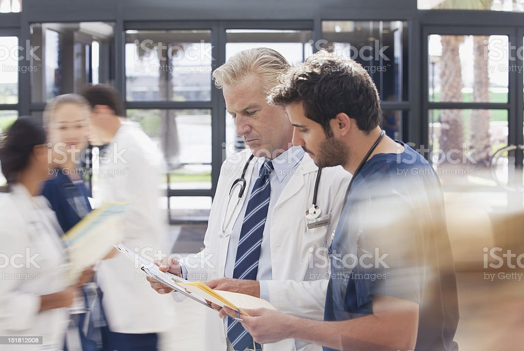 Doctor and nurse reviewing medical record in hospital stock photo