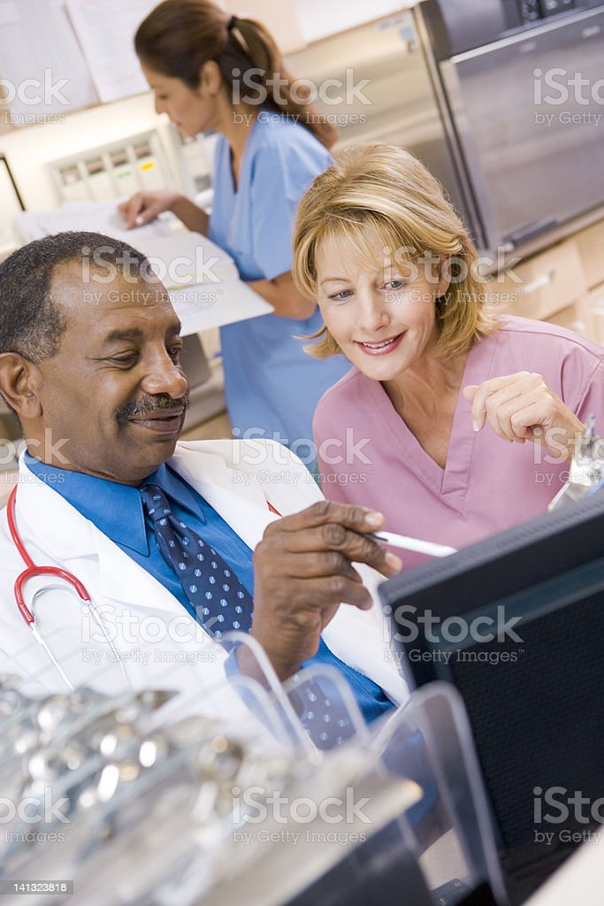 Doctor And Nurse Talking In The Reception Area stock photo