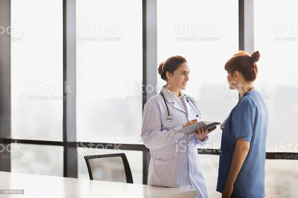 Doctor and nurse talking together in office stock photo