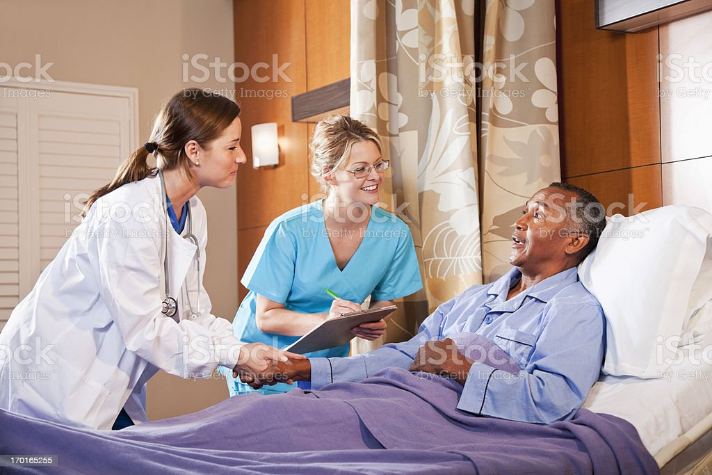 Doctor and nurse with patient in hospital bed royalty-free stock photo