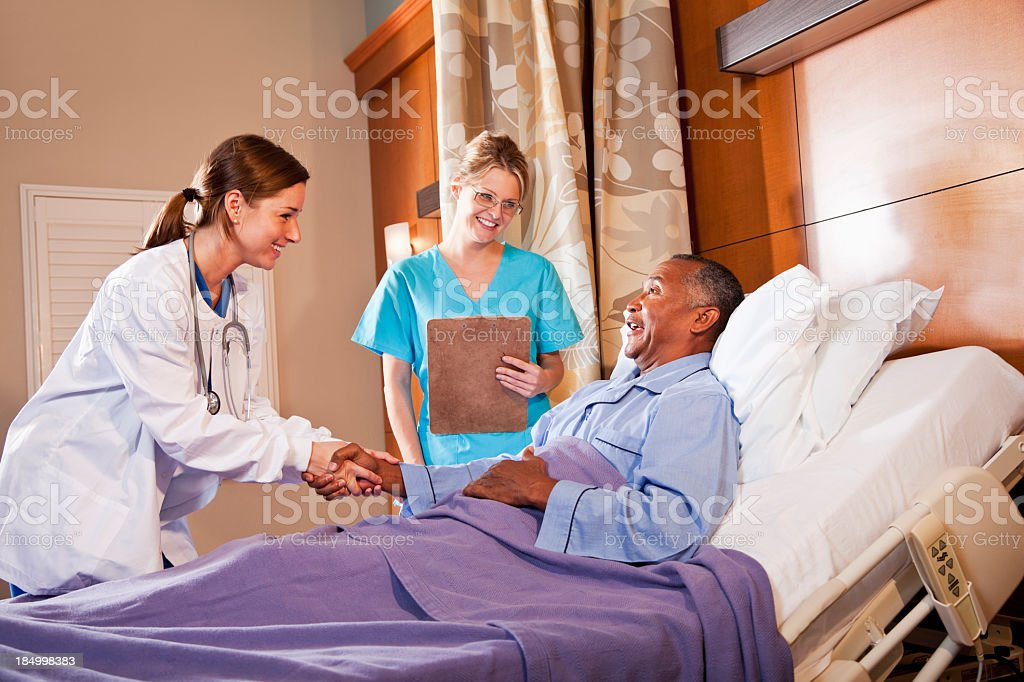 Doctor and nurse with patient in hospital bed stock photo