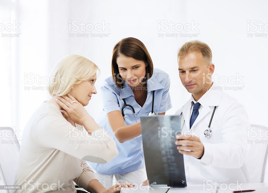 doctor and nurse with patient looking at x-ray stock photo
