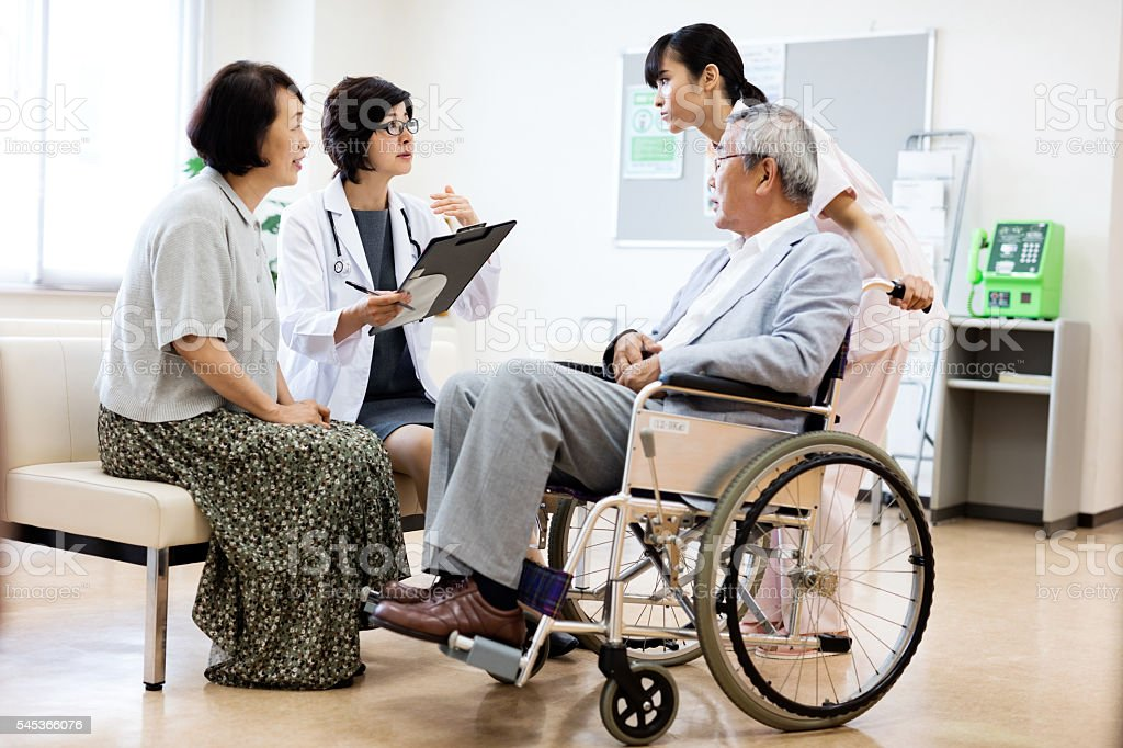 Doctor and nurse with senior couple in hospital stock photo