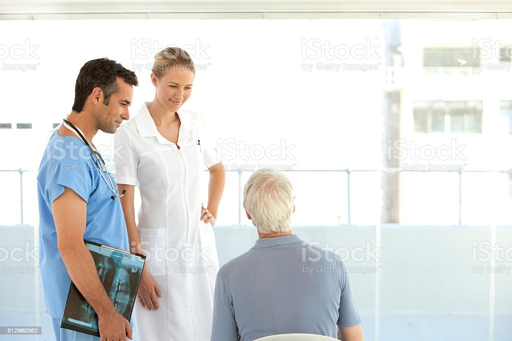 Doctor and nurse with senior patient stock photo
