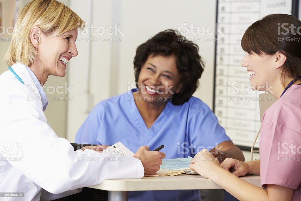 Doctor And Nurses In Discussion At Nurse Station royalty-free stock photo