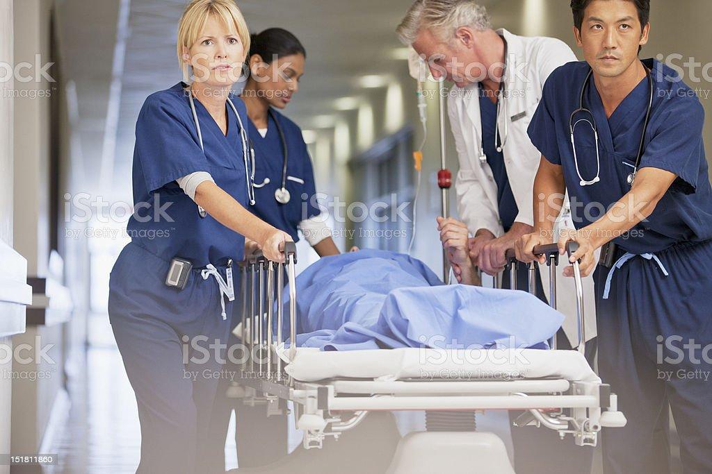 Doctor and nurses wheeling patient in gurney down hospital corridor stock photo