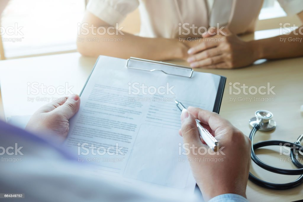 Doctor and patient are discussing something, just hands at the table. stock photo
