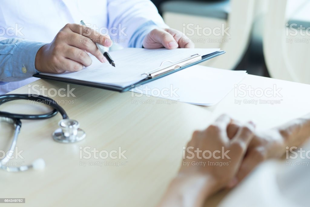 Doctor and patient are discussing something, just hands at the table stock photo
