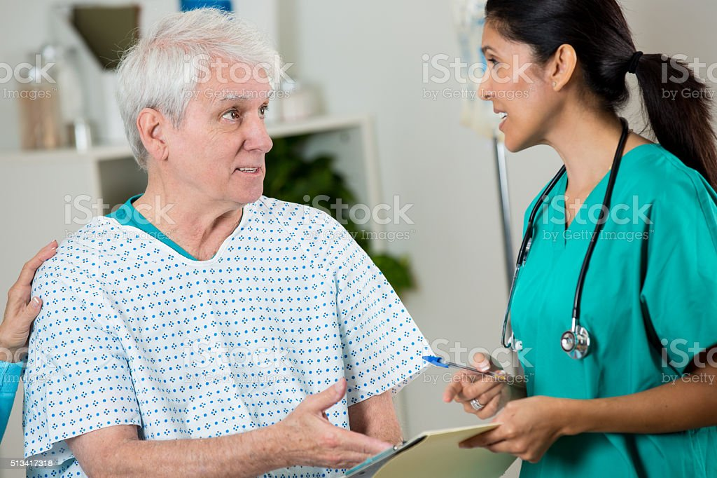 Doctor and patient discuss diagnosis stock photo