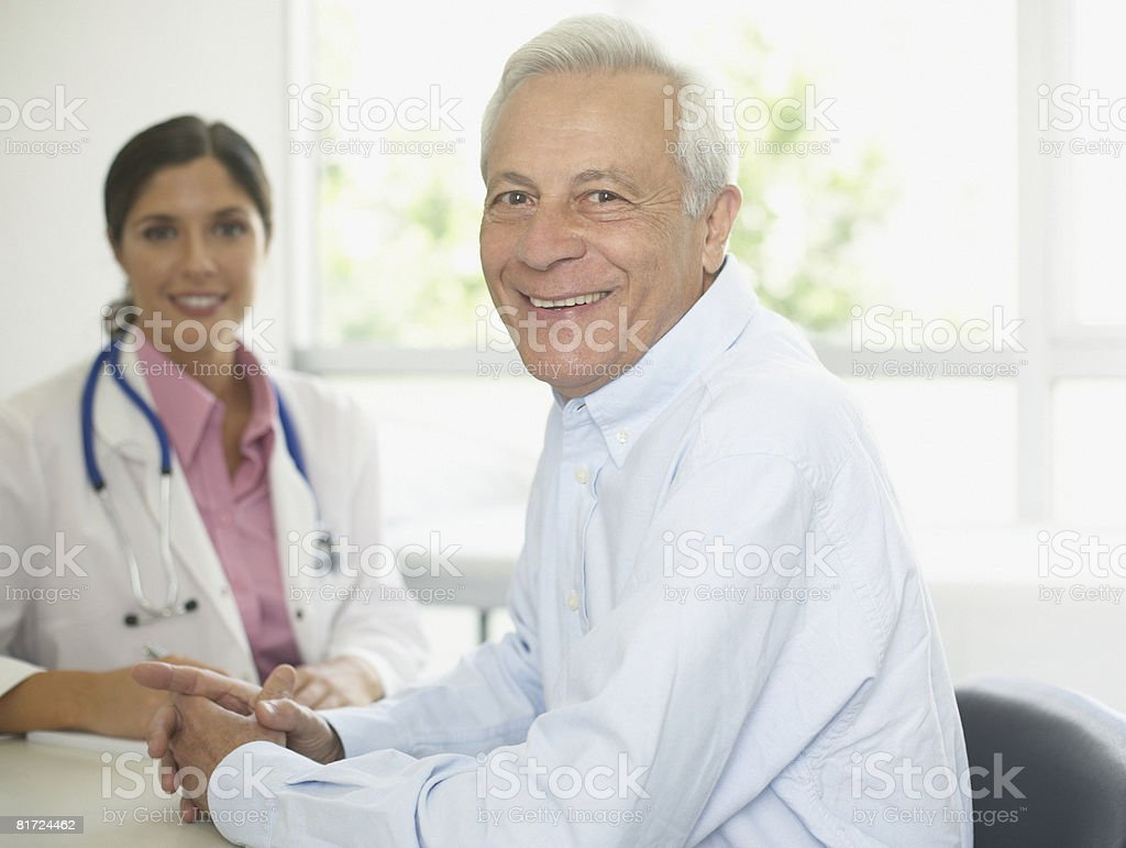 Doctor and patient sitting in office smiling royalty-free stock photo