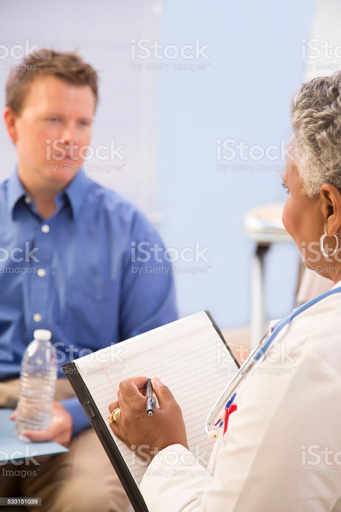 Doctor appointment with mid-adult man patient. Therapy. Consulation. stock photo
