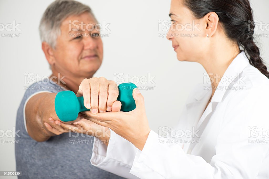 Doctor Assisting Senior Patient In Lifting Dumbbell stock photo