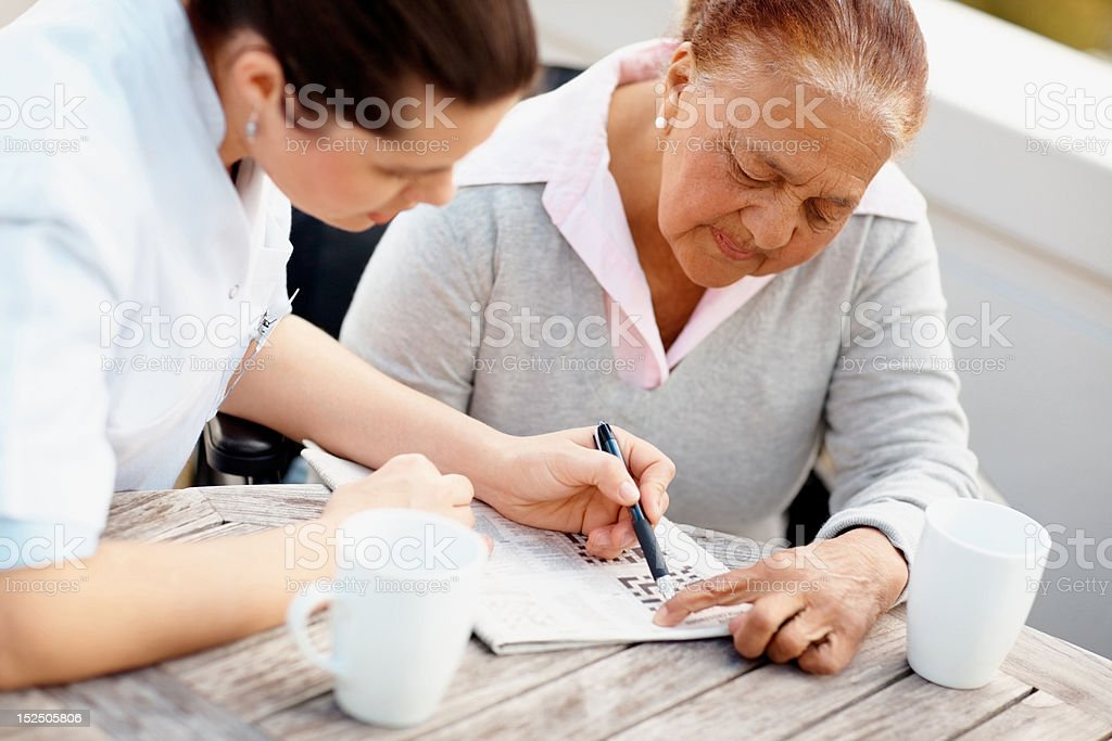 Doctor assisting senior patient to solve crossword stock photo
