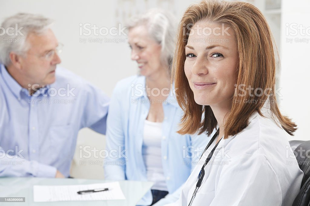 Doctor at Office With Happy Senior Adult Patient and Spouse royalty-free stock photo
