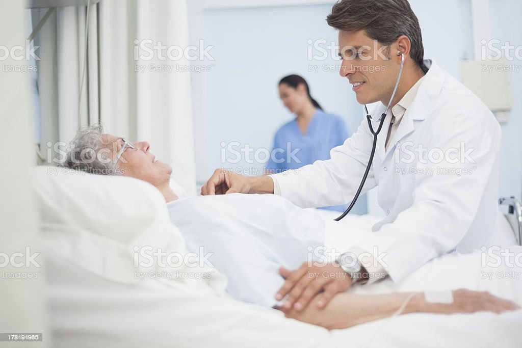 Doctor auscultating a patient royalty-free stock photo