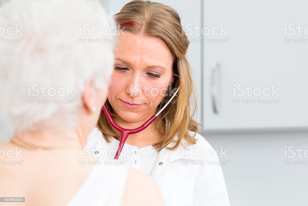 Doctor auscultating senior patient in practice stock photo