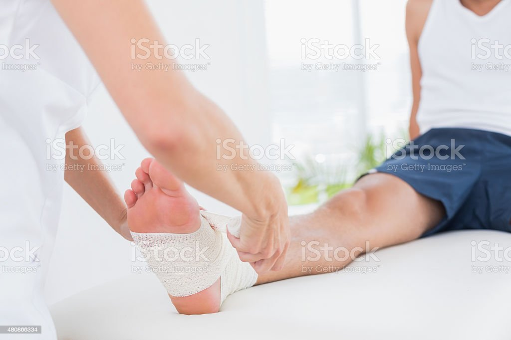 Doctor bandaging her patient ankle stock photo