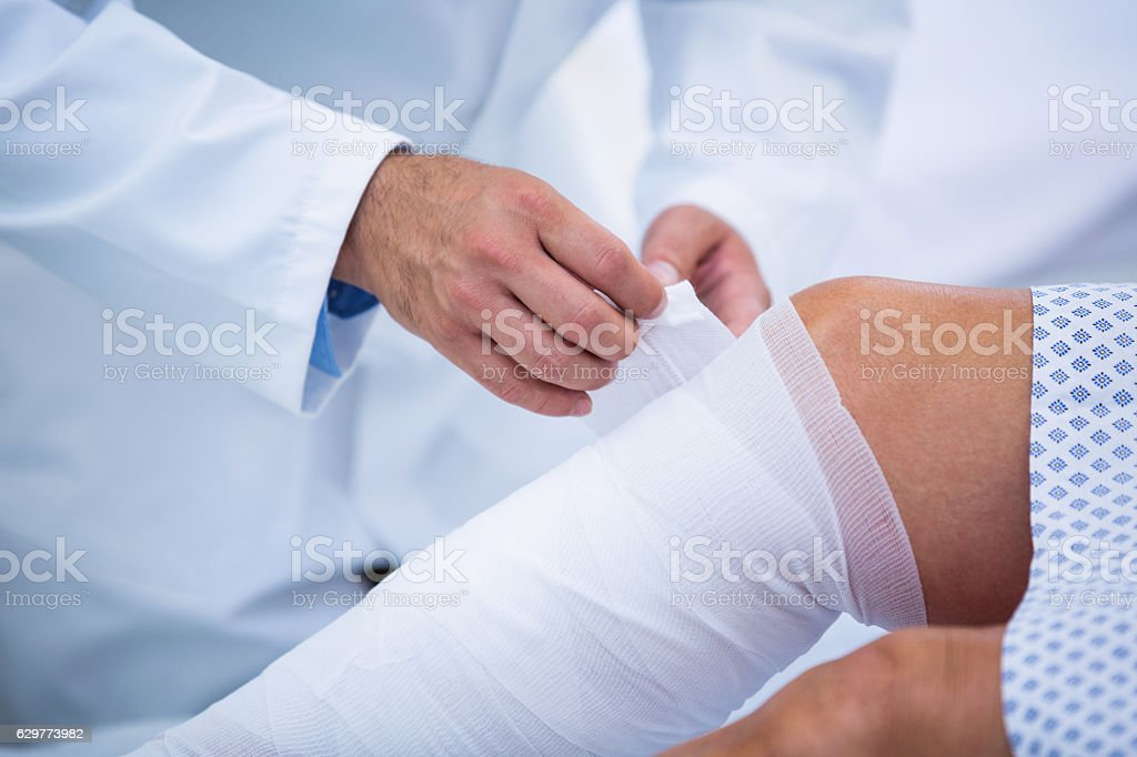 Doctor bandaging leg of patient stock photo