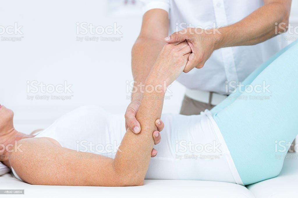 Doctor bending his patient arm stock photo