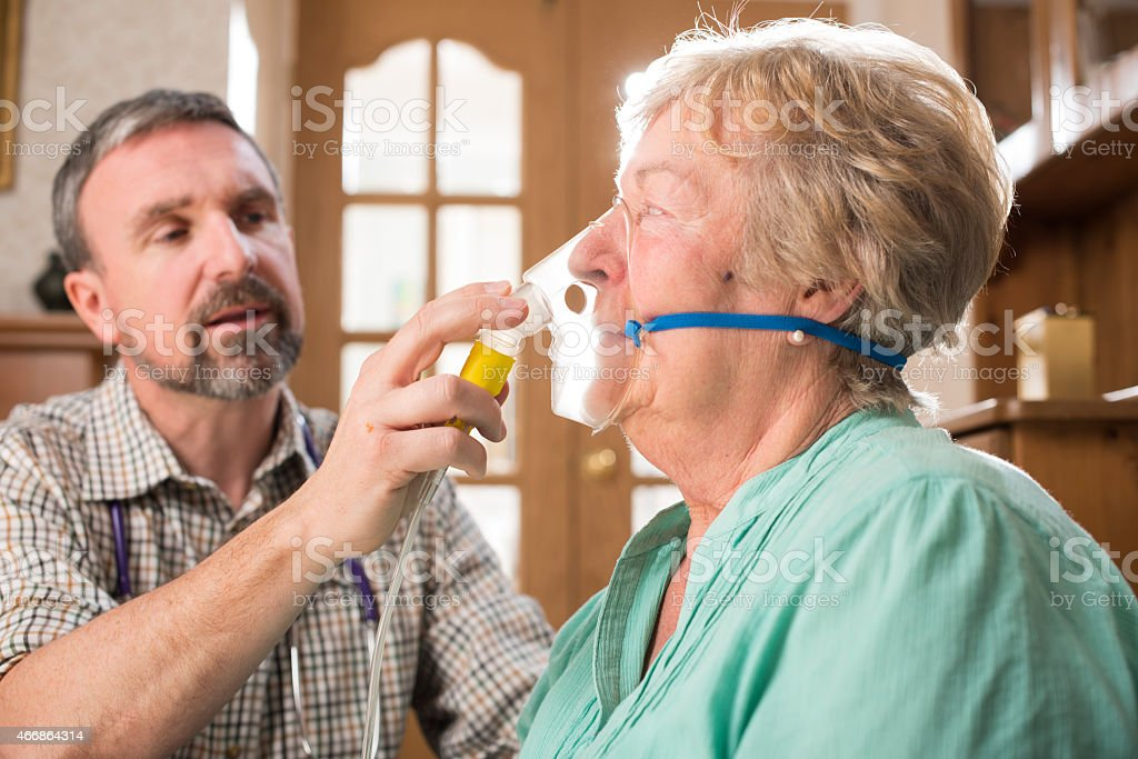 Doctor calms his asthma patient down stock photo
