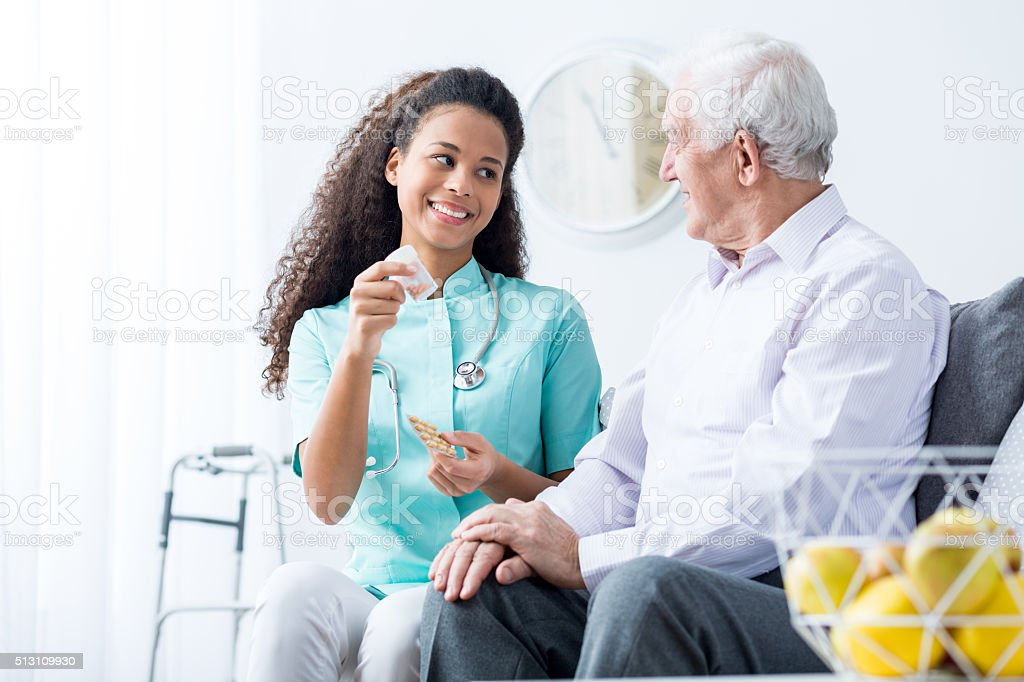 Doctor caring about elder person stock photo