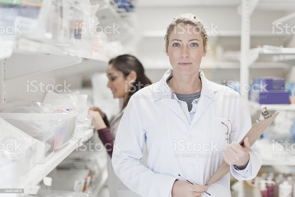Doctor carrying clipboard in hospital stock photo