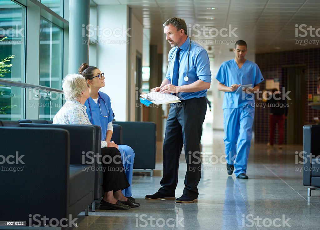 doctor chatting to a patient on the hospital corridor. stock photo