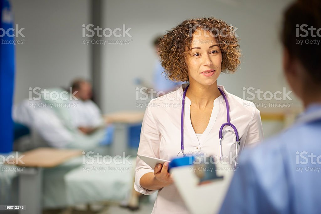 doctor chatting to nurse on ward stock photo