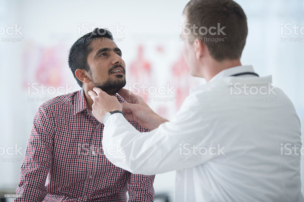 Doctor Checking a Man's Lymph Nodes stock photo