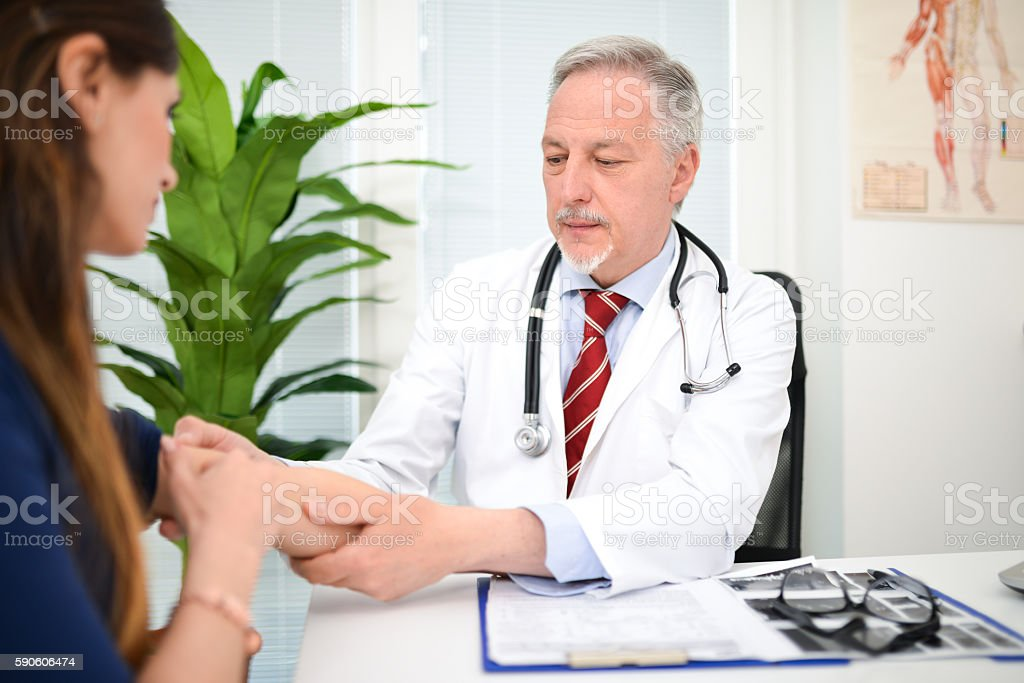 Doctor checking a patient's arm stock photo