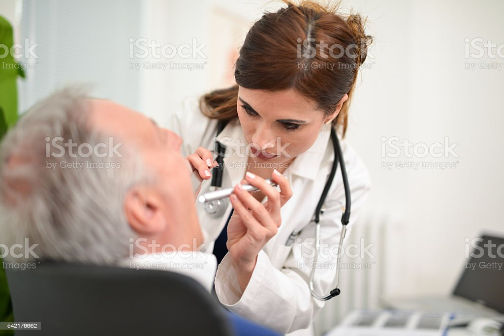 Doctor checking a patient's throat stock photo