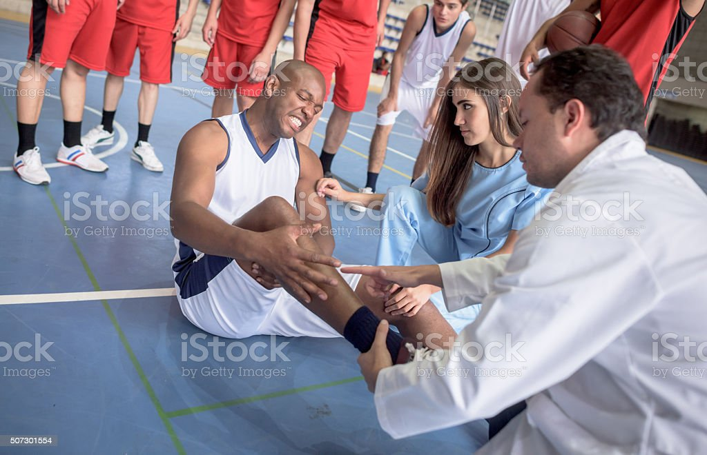 Doctor checking an ankle injury at a basketball game stock photo