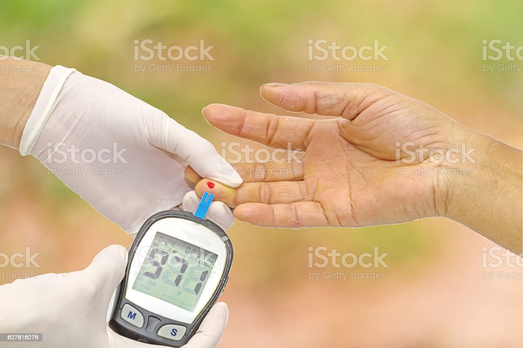 Doctor checking blood glucose on  finger and pink bokeh background. stock photo