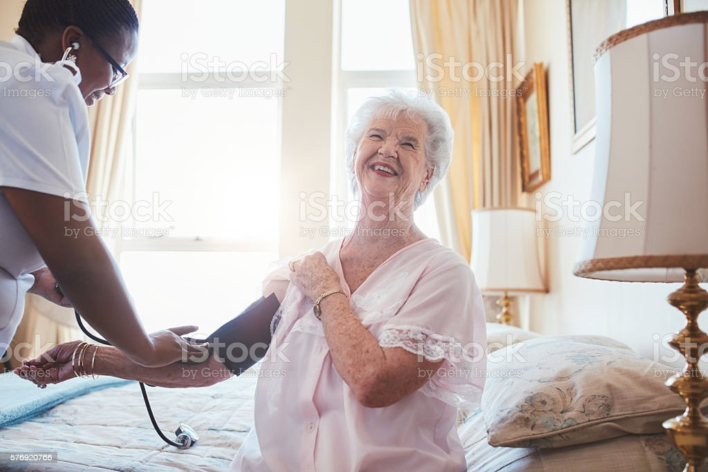 Doctor checking blood pressure of a senior woman stock photo