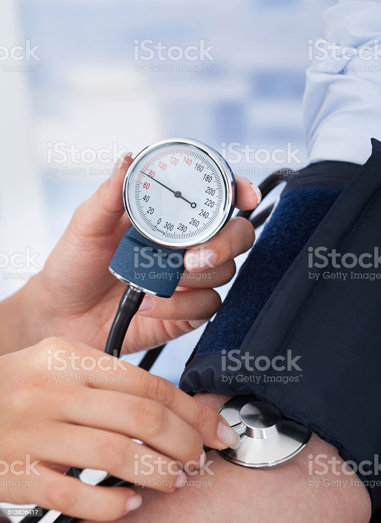 Doctor Checking Blood Pressure Of Businessman stock photo