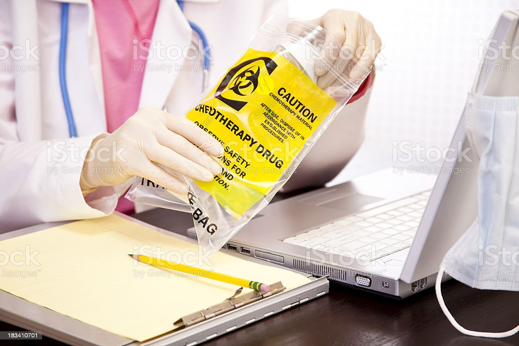 Doctor checking chemotherapy medication used by leukemia patient. Laptop. royalty-free stock photo