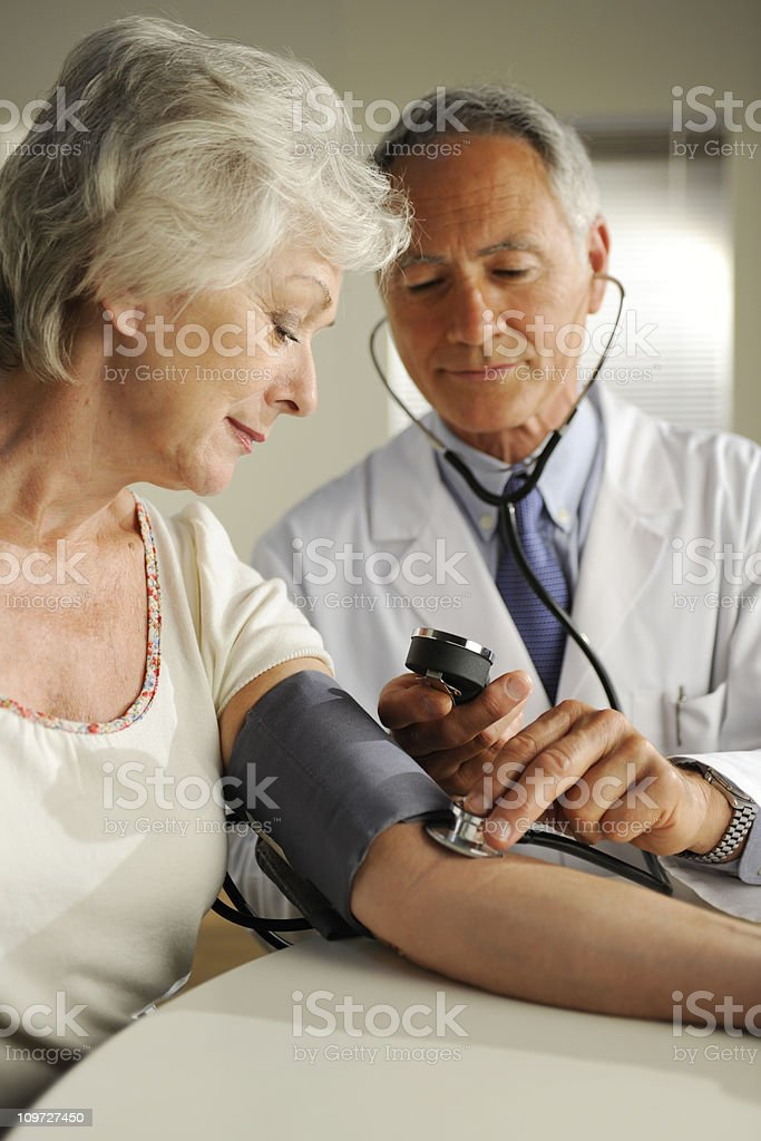 Doctor Checking Elderly Patient's Blood Pressure royalty-free stock photo