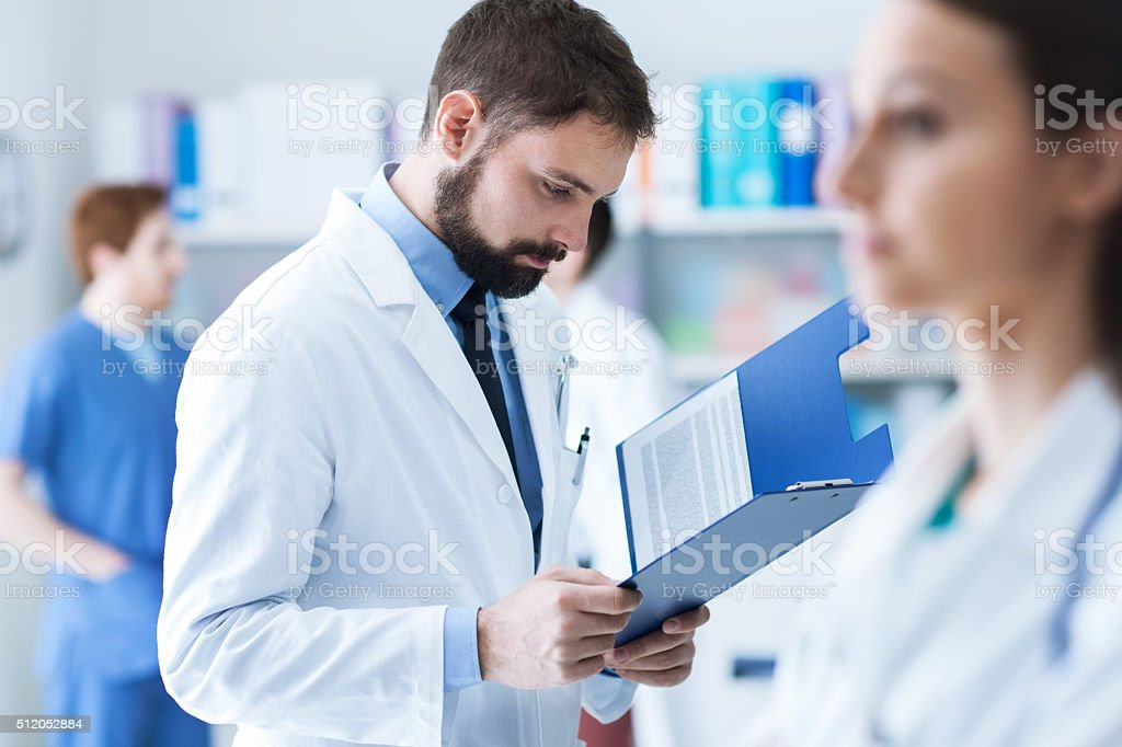 Doctor checking medical records stock photo