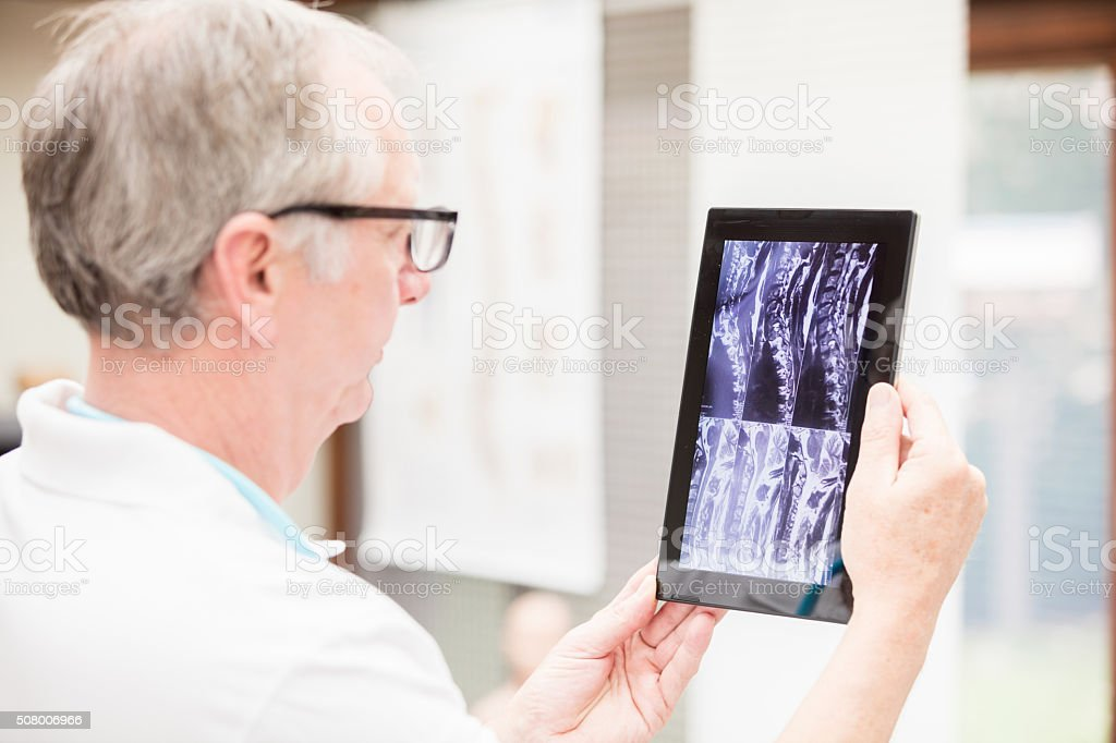 Doctor checking MRI images on tablet PC stock photo
