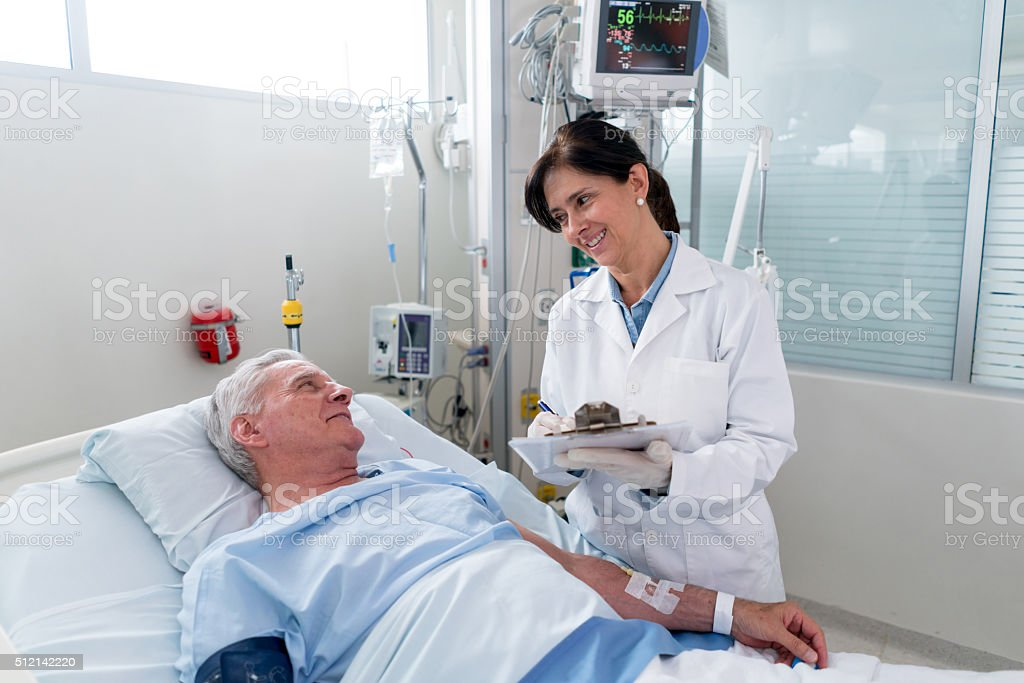 Doctor checking on a patient at the ICU stock photo