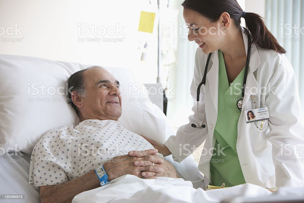 Doctor checking on older man stock photo