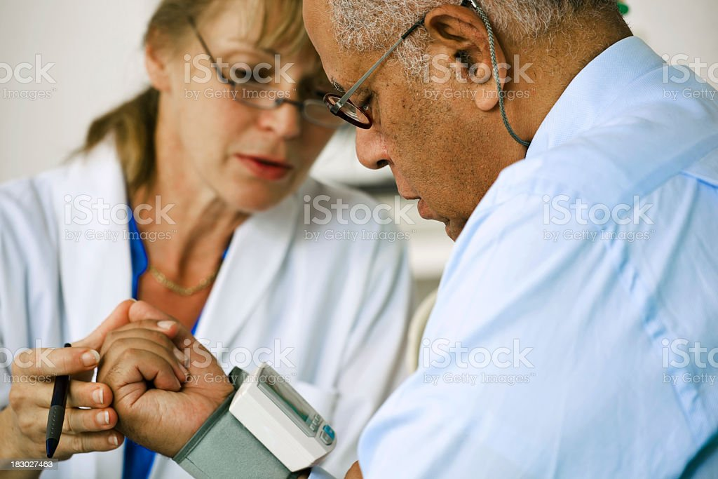 Doctor Checking the Blood Pressure of Her Patient stock photo