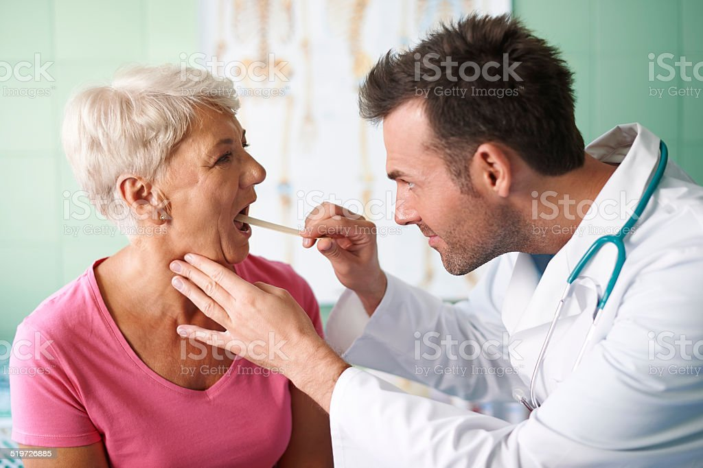 Doctor checking throat of senior woman stock photo