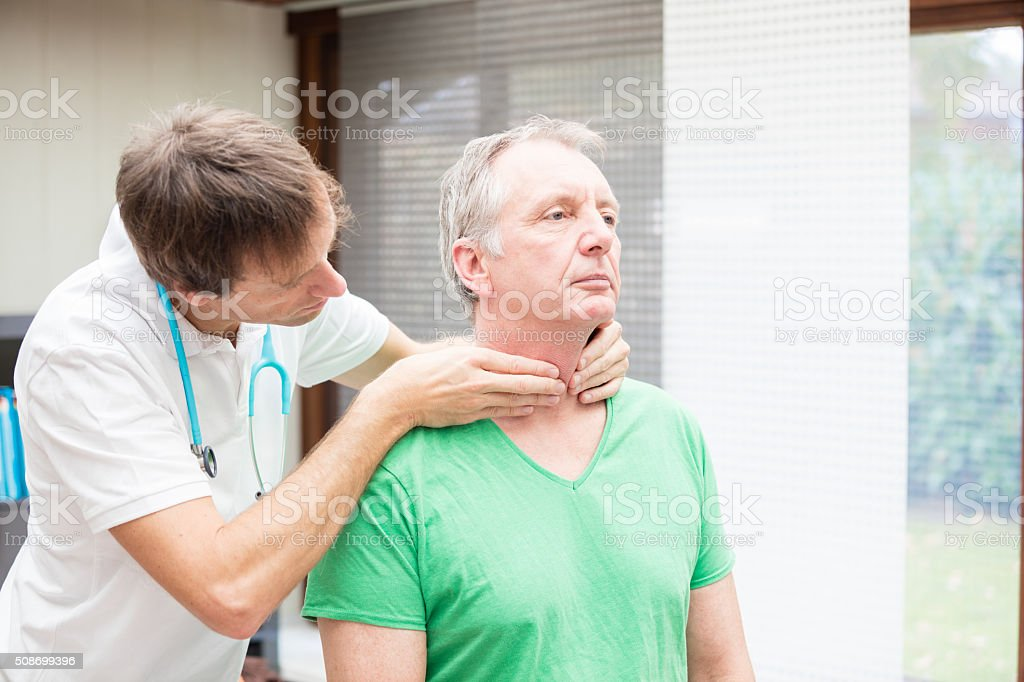 Doctor checking thyroidea of mature patient stock photo