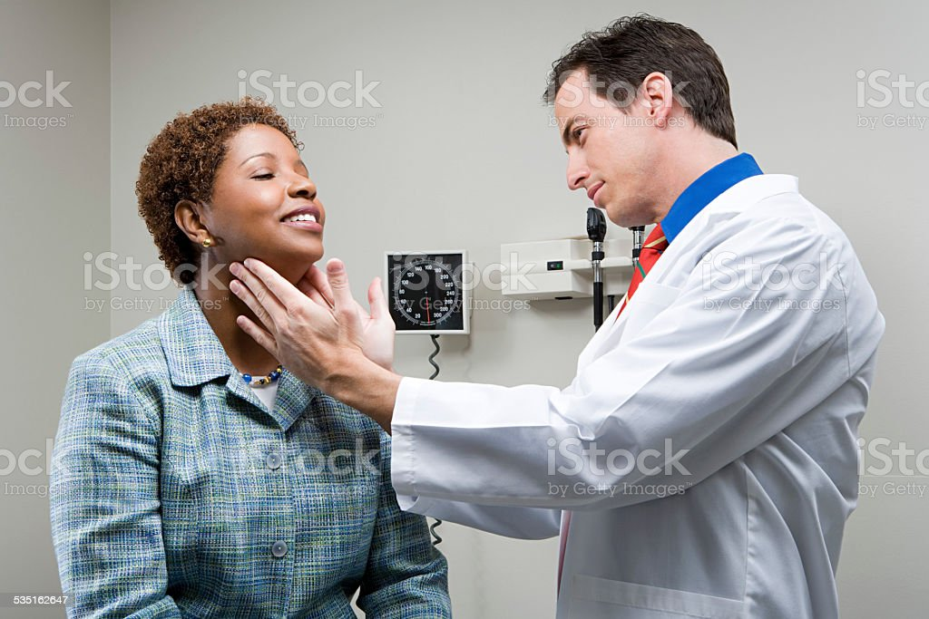 Doctor checking womans throat stock photo